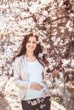 Mujer embarazada en las ramas florecientes Fotos de archivo libres de regalías