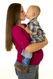 Mujer embarazada en muchacho rojo del beso del lado de la camisa Imagenes de archivo