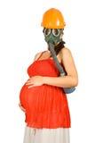 Mujer embarazada en sombrero duro y gas-máscara Imagen de archivo libre de regalías