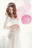 Mujer embarazada en un camisón blanco con los globos Imagen de archivo libre de regalías