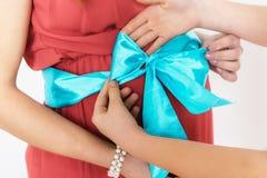 Mujer embarazada en un vestido rojo Su estómago atado con la cinta azul y el arco Las manos de su arco atado hija Imagenes de archivo