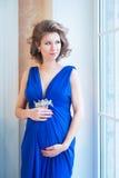 Mujer embarazada en vestido azul cerca de la ventana Fotos de archivo libres de regalías