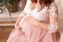 Mujer embarazada en vestido rosado hermoso foto de archivo