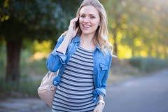 Mujer embarazada encantada que disfruta de la conversación sobre el teléfono al aire libre Imagen de archivo libre de regalías