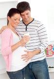 Mujer embarazada encantada que sostiene un vidrio de leche Imagenes de archivo