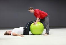 Mujer embarazada + entrenamiento personal del amaestrador Foto de archivo libre de regalías
