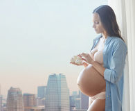 Mujer embarazada feliz con botines del bebé en casa Fotos de archivo libres de regalías