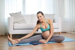 Mujer embarazada feliz con el ejercicio de la PC de la tableta Imagenes de archivo