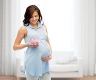 Mujer embarazada feliz con el piggybank Imagen de archivo