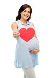 Mujer embarazada feliz con el vientre conmovedor del corazón rojo Foto de archivo libre de regalías