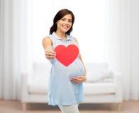 Mujer embarazada feliz con el vientre conmovedor del corazón rojo Foto de archivo