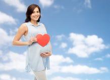 Mujer embarazada feliz con el vientre conmovedor del corazón rojo Fotografía de archivo libre de regalías
