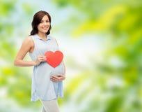 Mujer embarazada feliz con el vientre conmovedor del corazón rojo Imagenes de archivo