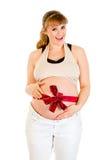 Mujer embarazada feliz con la cinta roja en el vientre Fotografía de archivo libre de regalías