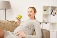 Mujer embarazada feliz con la manzana verde foto de archivo libre de regalías