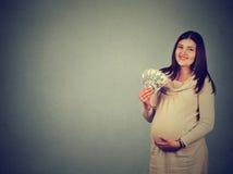 Mujer embarazada feliz con las cuentas de los billetes de banco del dólar del efectivo Fotografía de archivo libre de regalías