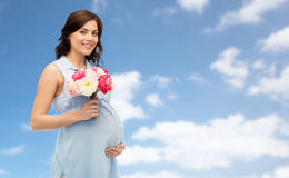 Mujer embarazada feliz con las flores sobre el cielo azul Imagen de archivo libre de regalías
