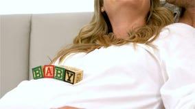 Mujer embarazada feliz con los cubos del bebé en el vientre almacen de video