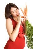 mujer embarazada feliz de 21 semanas con las zanahorias frescas Imágenes de archivo libres de regalías
