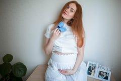 Mujer embarazada feliz en casa sosteniendo los calcetines azules para el bebé Fotos de archivo libres de regalías