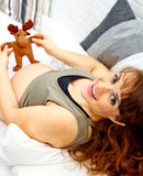 Mujer embarazada feliz en el juguete de la explotación agrícola del sofá. Primer Imagen de archivo libre de regalías