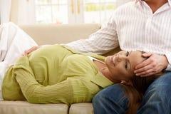 Mujer embarazada feliz en el sofá Imágenes de archivo libres de regalías