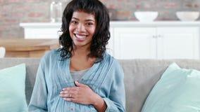 Mujer embarazada feliz en el sofá almacen de video