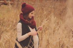 Mujer embarazada feliz en equipo acogedor suavemente caliente que camina al aire libre Foto de archivo libre de regalías