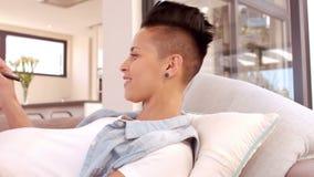 Mujer embarazada feliz en la escritura del sofá en la libreta almacen de metraje de vídeo