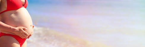Mujer embarazada feliz en la playa Imagen de archivo