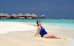 Mujer embarazada feliz en la playa, Maldivas Imagenes de archivo