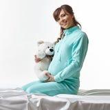 Mujer embarazada feliz en ropa casual con el juguete Imagenes de archivo