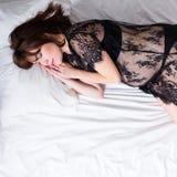 Mujer embarazada feliz en ropa interior negra del cordón que duerme en cama Imágenes de archivo libres de regalías