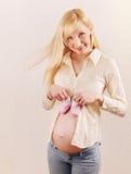 Mujer embarazada feliz linda que cuenta con a un bebé con poco rosa Imágenes de archivo libres de regalías