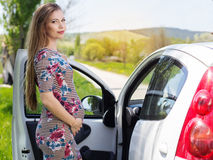 Mujer embarazada feliz que coloca el coche cercano Imagenes de archivo