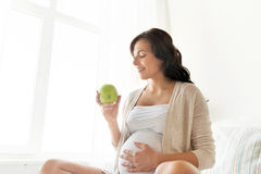 Mujer embarazada feliz que come la manzana verde en casa fotos de archivo