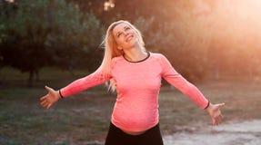 Mujer embarazada feliz que disfruta del momento, puesta del sol Fotografía de archivo