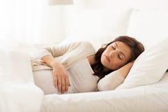 Mujer embarazada feliz que duerme en cama en casa Fotos de archivo