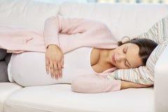 Mujer embarazada feliz que duerme en el sofá en casa Fotografía de archivo