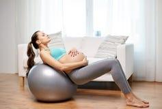 Mujer embarazada feliz que ejercita en fitball en casa Foto de archivo libre de regalías