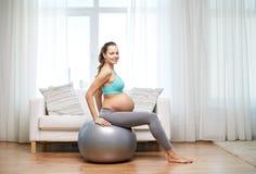 Mujer embarazada feliz que ejercita en fitball en casa Foto de archivo