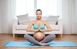 Mujer embarazada feliz que medita en casa Fotos de archivo