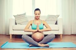 Mujer embarazada feliz que medita en casa Imágenes de archivo libres de regalías