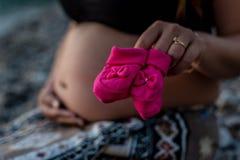 Mujer embarazada feliz que se sienta en la playa con los zapatos de bebé Fotos de archivo
