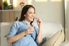 Mujer embarazada feliz que toma una píldora en casa imagen de archivo libre de regalías