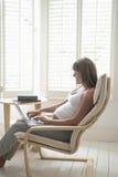 Mujer embarazada feliz que usa el ordenador portátil en silla Imágenes de archivo libres de regalías