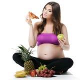 Mujer embarazada, fruta y pizza, consumición sana fotografía de archivo libre de regalías