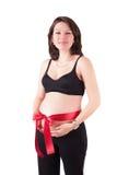 Mujer embarazada hermosa con la cinta roja Fotos de archivo libres de regalías