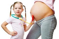Mujer embarazada hermosa con su hija Foto de archivo