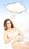 Mujer embarazada hermosa en cama con la nube conceptual Imágenes de archivo libres de regalías